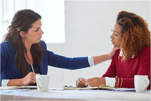 Stock image of two women talking in an office.