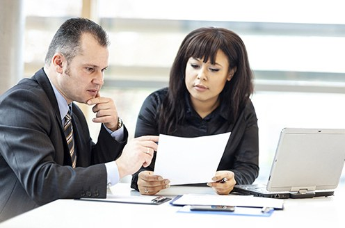 Stock image of a man and a woman studying a piece of paper in a conference room with a laptop on the table.