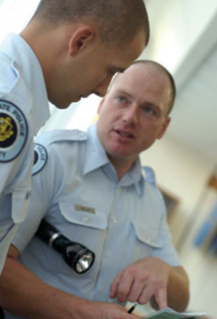 Two police professionals discuss work-related feedback. © Mark C. Ide