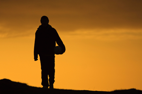 Stock image of an individual walking along a lonely road at sunset.