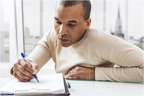 Stock image of a man writing in a notebook in an office setting.