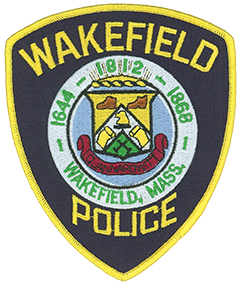 "The Wakefield, Massachusetts, Police Department patch features the town's seal. Consisting of twin circles, it signifies Wakefield's history, industrial development, and scenic beauty. The outer circle frames three dates: 1644, commemorating the town's incorporation as Reading; 1812, when it became South Reading; and 1868, when the name changed to Wakefield. A shield centers the inner circle and bears symbols of the industries prominent in local development—shoes, rattan, and metal casting. Its middle features the heraldic eagle. Above the shield are the reflecting rays of the rising sun. Below, the name ""Quannapowitt"" identifies one of the Native Americans who signed the deed to white settlers in 1868."