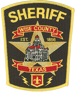 "Wise County, Texas, was founded in 1856 and is named after U.S. Congressman Henry A. Wise of Virginia, who had supported Texas' annexation by the United States. The patch of the Wise County Sheriff's Office features a large gold star beneath two red banners showcasing the county and state names, respectively. The visually stunning Wise County Courthouse is depicted atop the star. Built in 1896 of pink granite and marble, the courthouse is the third to serve the county since its founding, the first two falling victim to arson. The emblem of the ""Lost Battalion"" is shown at the bottom of the patch. In March 1942, the battalion's members—most of whom were from western Texas—survived the sinking of the cruiser U.S.S. Houston and spent the next 42 months as prisoners of Japanese forces."