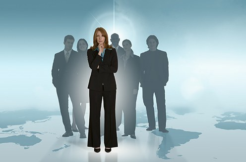 Stock image of a woman standing on a map with several others standing behind her.