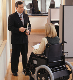 Stock image of two coworkers talking in an office setting.