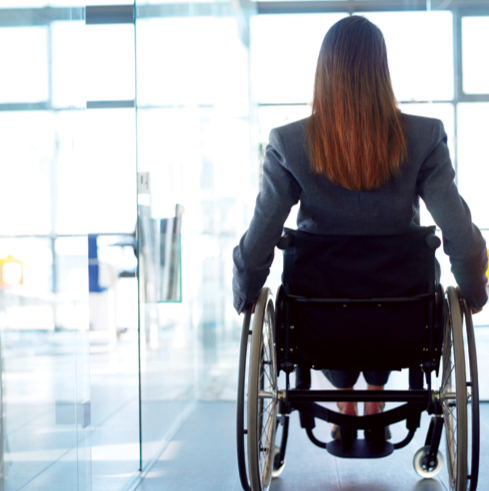 Stock image of a woman in a wheelchair making her way to her office. © Photos.com