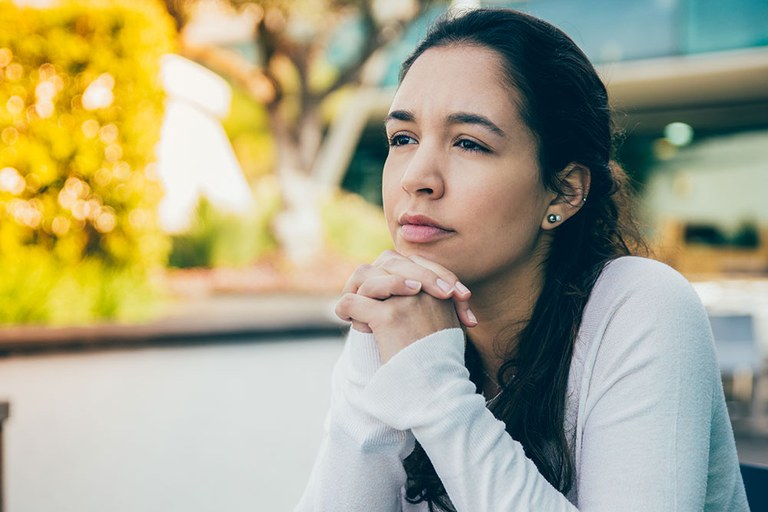 A stock image of a woman thinking.