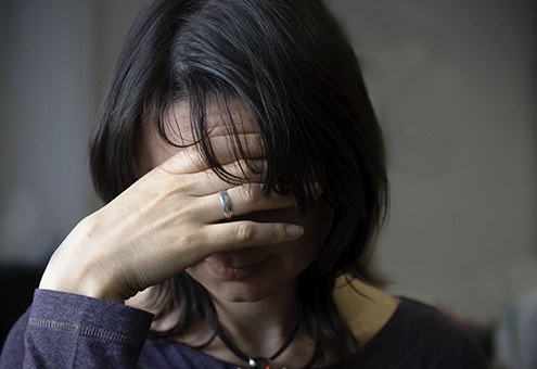 Stock image of a woman in distress with her hand over her face.