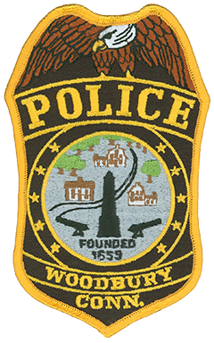 "Woodbury, Connecticut, first was settled in 1659 as part of Pomperaug Plantation, named after the nearby Pomperaug River. The town itself came to fruition in 1673 and was named for its function as a ""dwelling place in the woods."" The patch of the Woodbury Police Department prominently depicts the town's Soldiers' Monument within the center seal. Flanked by two cannons, the memorial obelisk was erected in 1871 in remembrance of Woodbury's 65 soldiers who died during the American Civil War. Traversing the patch is U.S. Route 6, referred to as the ""Grand Army of the Republic Highway."" Along the route are pictured several of Woodbury's colonial-era buildings. Today the town is known throughout the state as the ""Antiques Capital of Connecticut."""