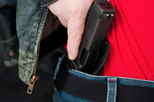 Stock image of a man pulling a gun from the waistband of his jeans.