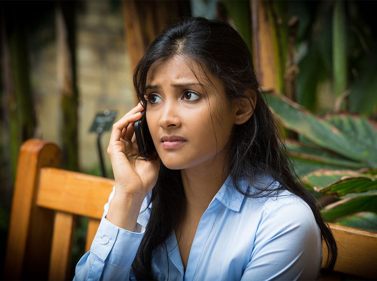 A stock image of a young lady on her cell phone looking worried.