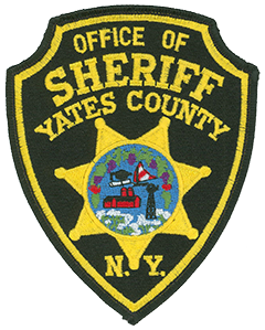 The arrowhead-shaped patch of the Yates County, New York, Sheriff's Office features the county seal in the center of a seven-point star. It depicts grapes, apples, and flowering buckwheat. The blue background represents three large lakes—Keuka, Canandaigua, and Seneca—and features symbols illustrating higher education, water recreation, farming, and rural commerce. The area is located in the heart of the Finger Lakes region.
