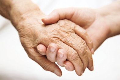 Stock image of a young adult lending a hand to an elderly person.